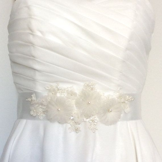 This is a very romantic bridal sash belt. It is made with a heavily beaded lace appliqué and hand made silk organza flowers. 3 larger silk organza flowers with Swarovski pearl centers are surrounded by several smaller satin faced silk and silk organza flowers. The embellishments are mounted on a Swiss double faced satin ribbon. This ribbon is 1.5 inches wide and 3 yards long. The decorated part of the belt is 8.5 inched long and 4 inches wide at the largest.