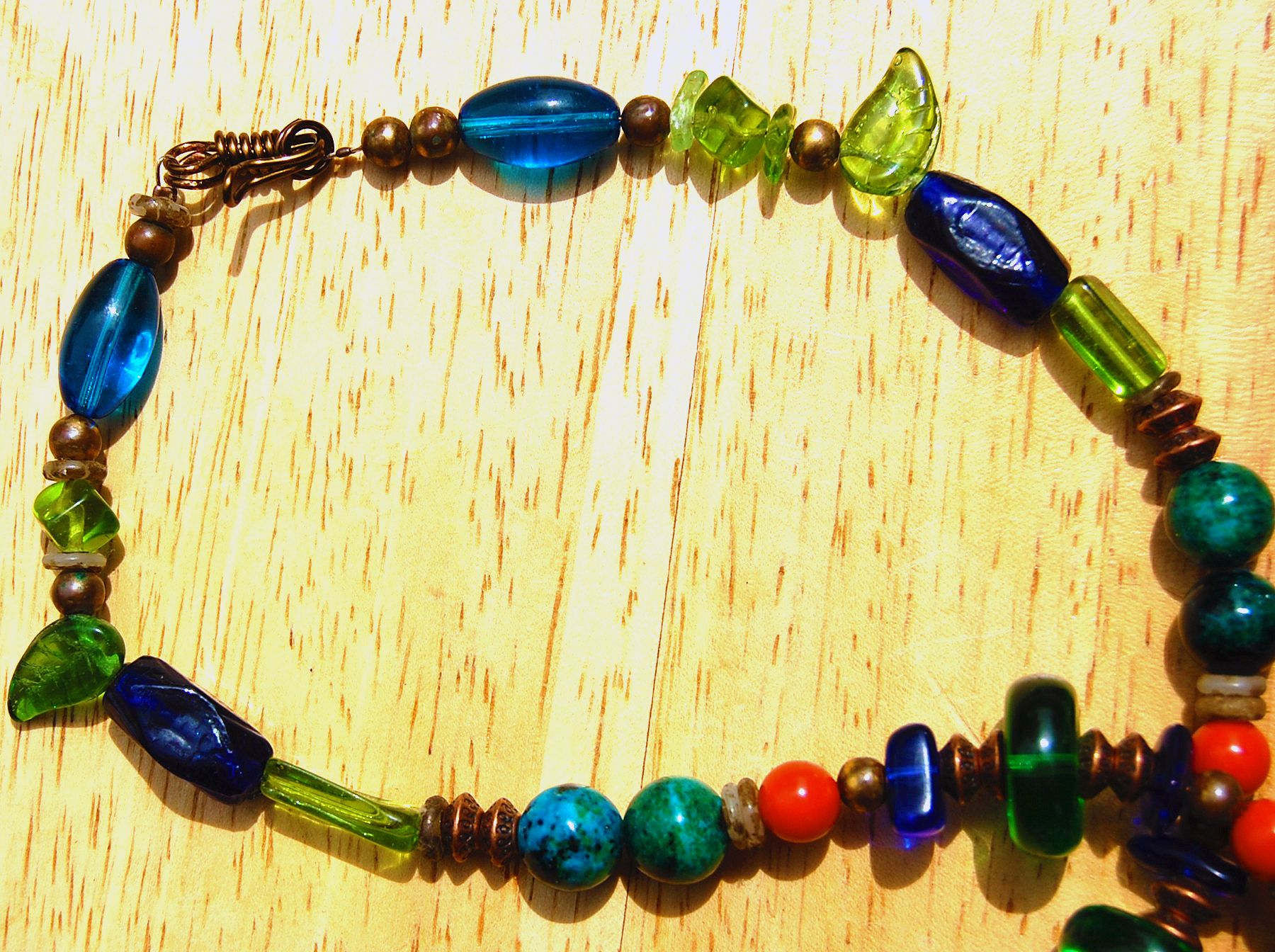 Showing vintage glass beads, antique copper 'saucer' spacers, vintage brass beads, tiny shell spacers and Azurite beads. I made the clasp from antique copper wire. The beads are strung with antique copper coated beaded wire and two antique copper crimping beads were used.