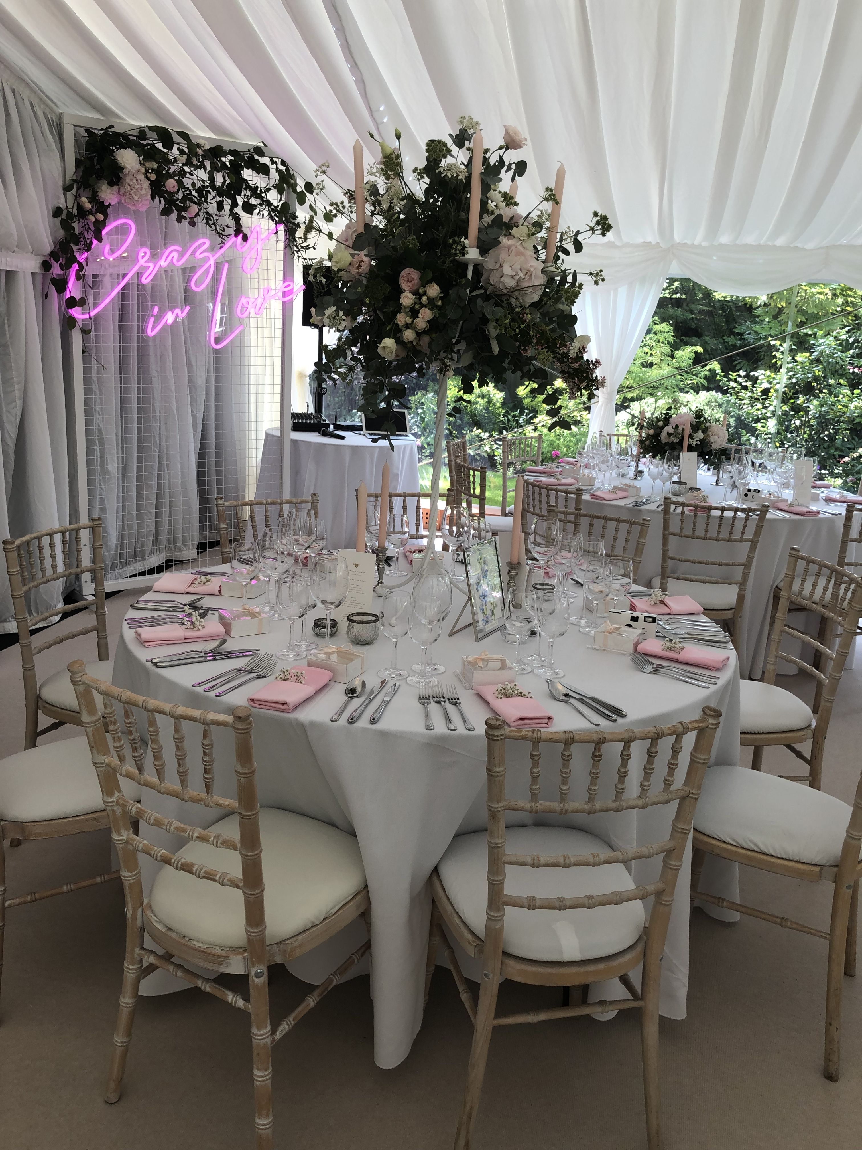 Crazy in love sign, table decor and white chiavari chairs with ivory seat pads #tabledecorations #tabledecor #weddinglighting #weddinglights #weddinginspiration #weddingdecorationideas #marqueewedding #marqueelights