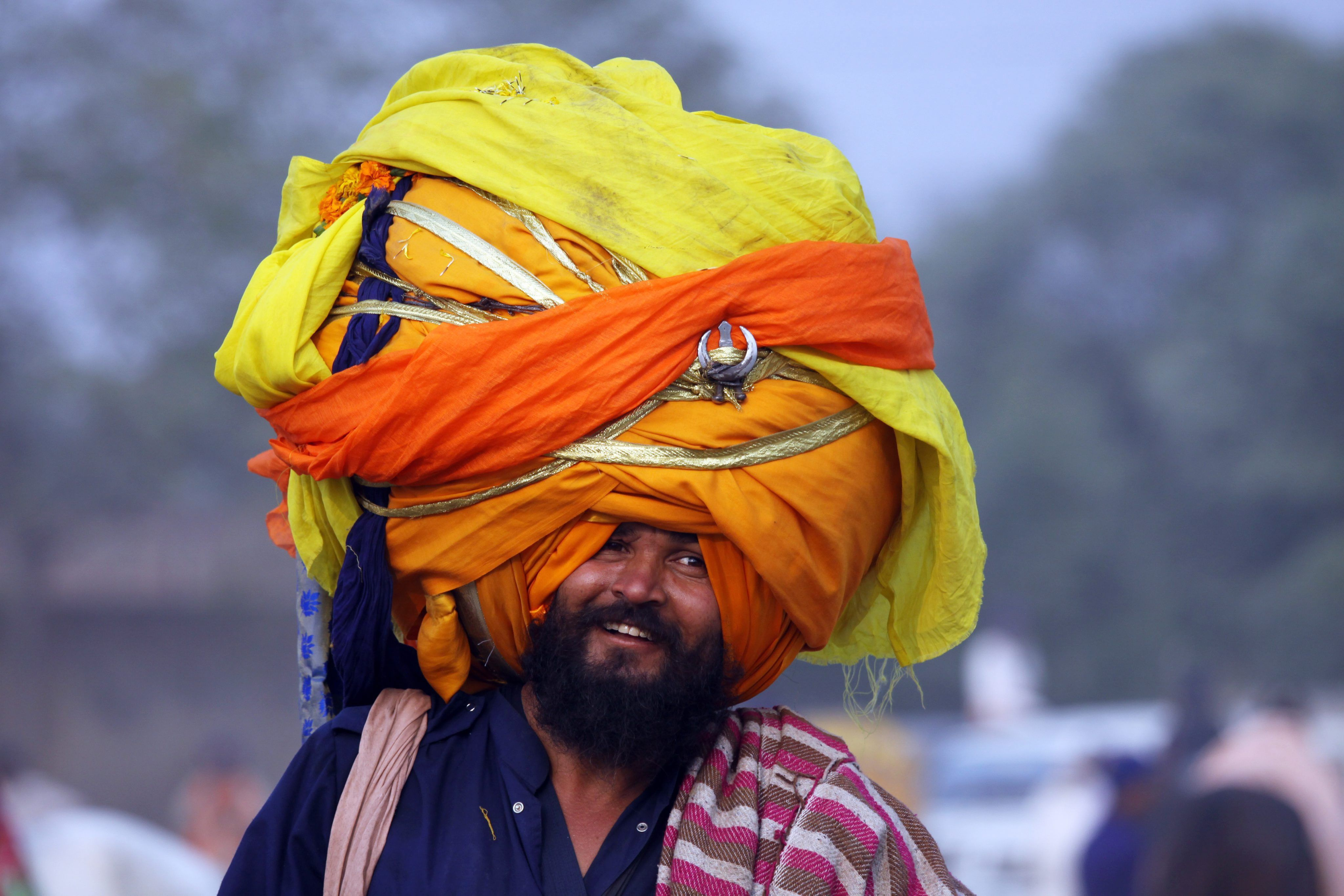 Pictures say a thousand words...An Indian 'Nihang' or a man whose ancestors belonged to Sikh warrior clan, smiles supporting an over-sized turban as he takes part in a religious procession called Mohalla in Amritsar, India. (Photo: Newscom)