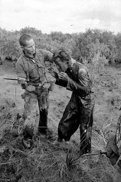 In this Jan. 9, 1964 photo, a South Vietnamese soldier uses the end of a dagger to beat a farmer for allegedly supplying government troops with inaccurate information about the movement of Viet Cong guerrillas in a village west of Saigon, Vietnam. (Photo by AP Photo/Horst Faas)