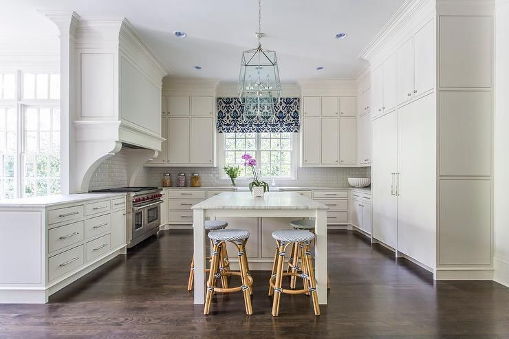Welcoming u-shaped kitchen is lit by two glass an nickel lanterns hung over a gray and white quartzite countertop complementing an off-white island finished with legs and seating four Serena & Lily Riviera Backless Barstools.