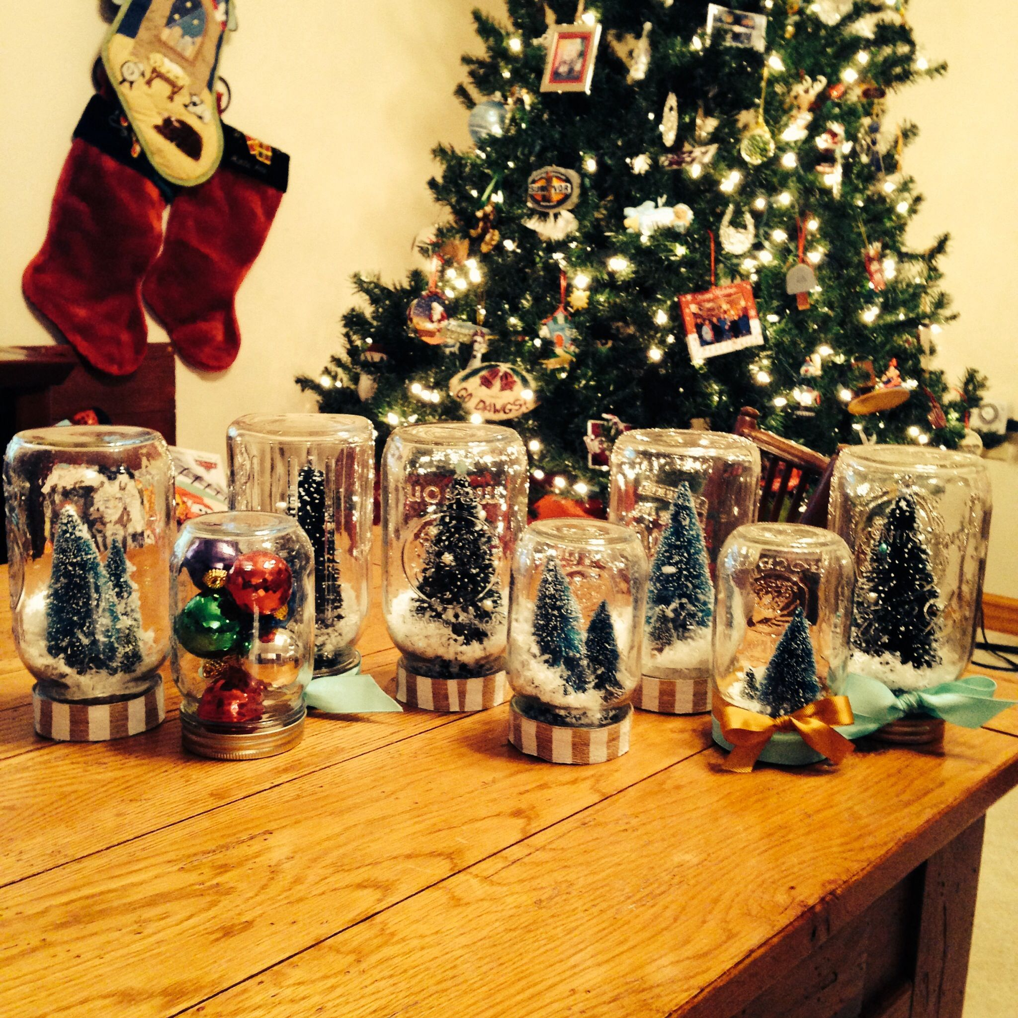 Christmas Mason Jar Snowglobes.....buy the tiny trees and fake snow at Hobby Lobby...glue trees to the bottom of the lid....and add snow....easy and elegant!