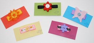 Hair barrettes featuring grosgrain ribbon & fun buttons; by two dot designs.