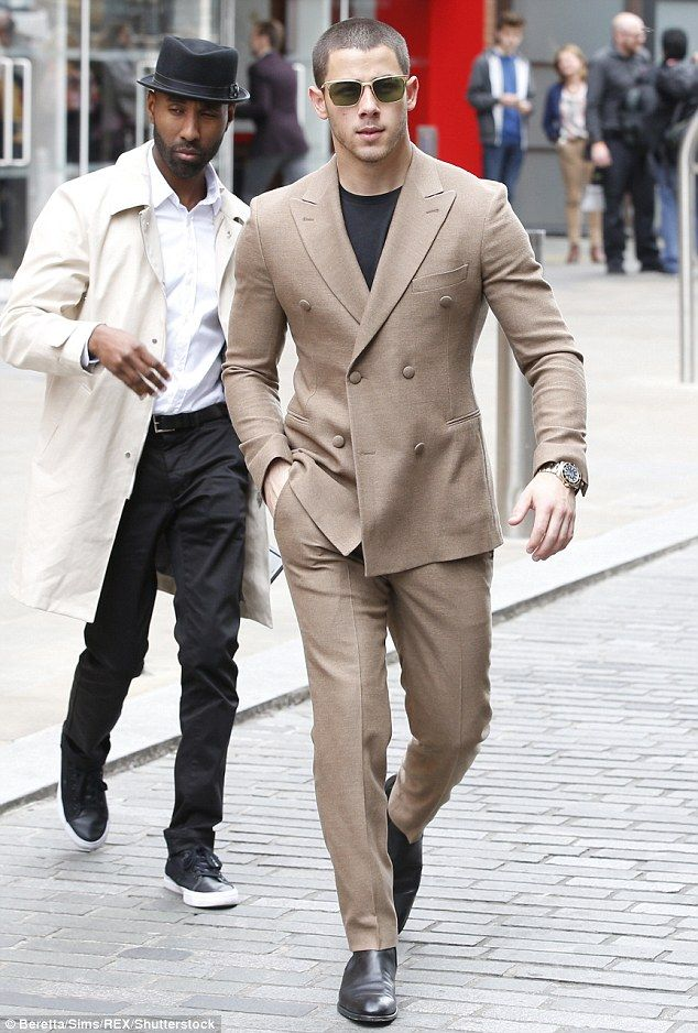 Nick Jonas cuts a smart figure in a beige two-piece suit as he arrives at Shakespeare's Gl...