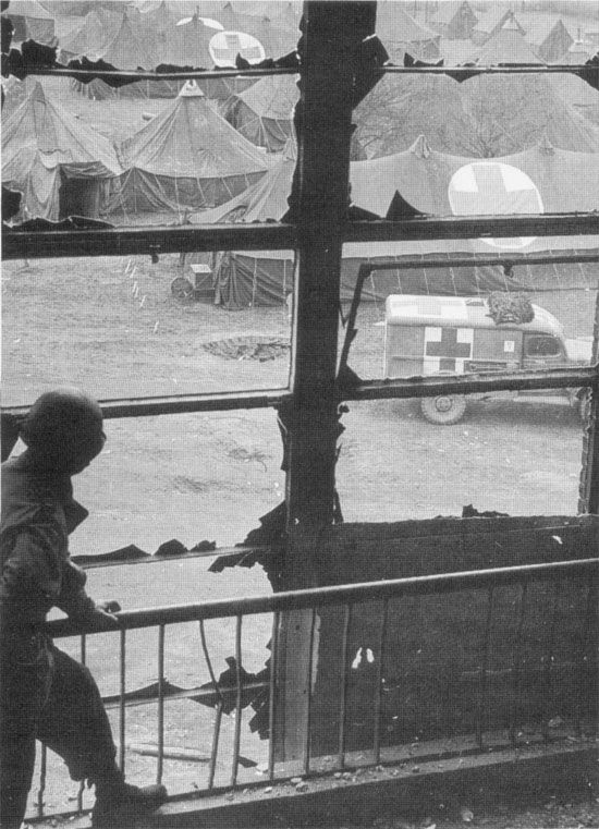A GI looks out over the tents and vehicles of the 48th