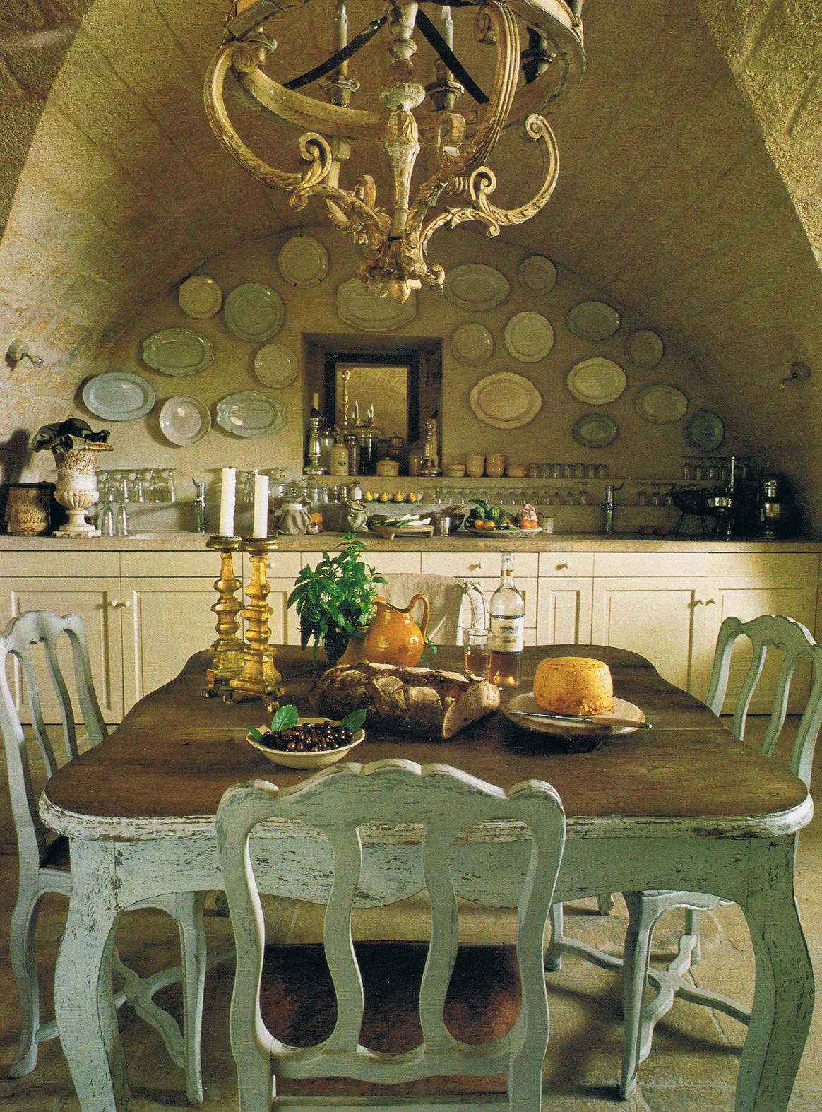 Vaulted ceiling in kitchen… baroque gilded chandelier over 19th century Swedish table    and 18th century French chairs…wall decorated with Moustiers and Sarreguemine faience plates…