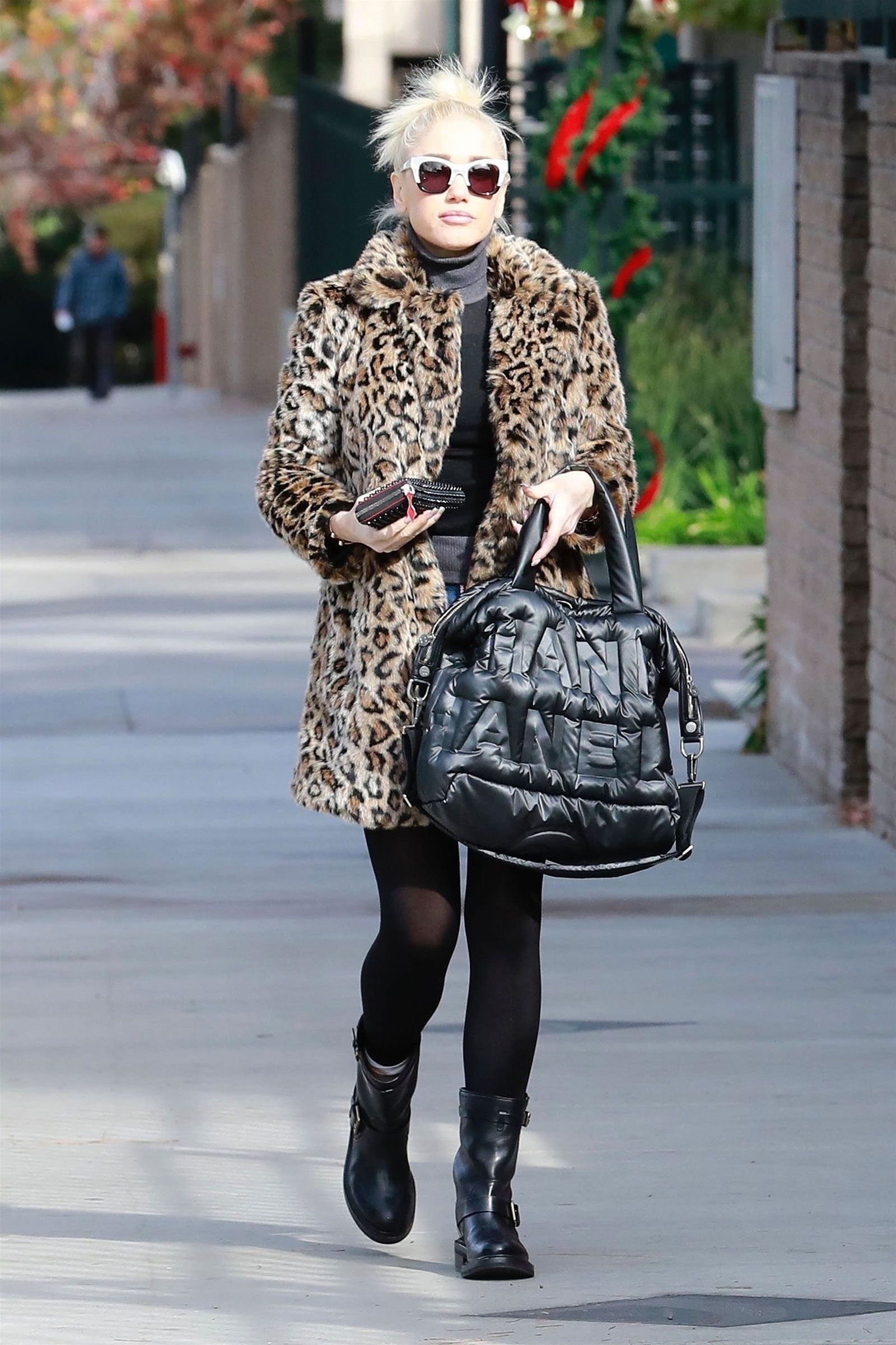 cc86cf5b9 Gwen Stefani wears a leopard Vince Camuto coat with moto boots and a Chanel  bag.