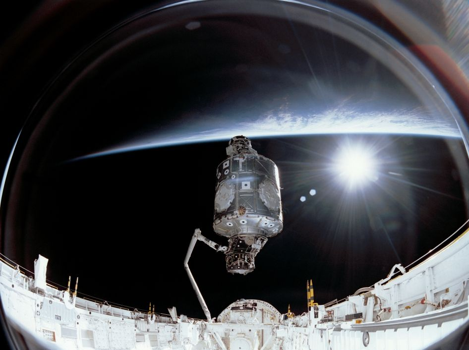 Image of U.S.-built Unity node being lifted out of Endeavour's payload bay to position it upright for connection to the Russian-built Zarya module.