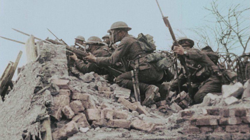 1918:  Ein britisches Bataillon geht zwischen zertrümmerten Häusern eines...