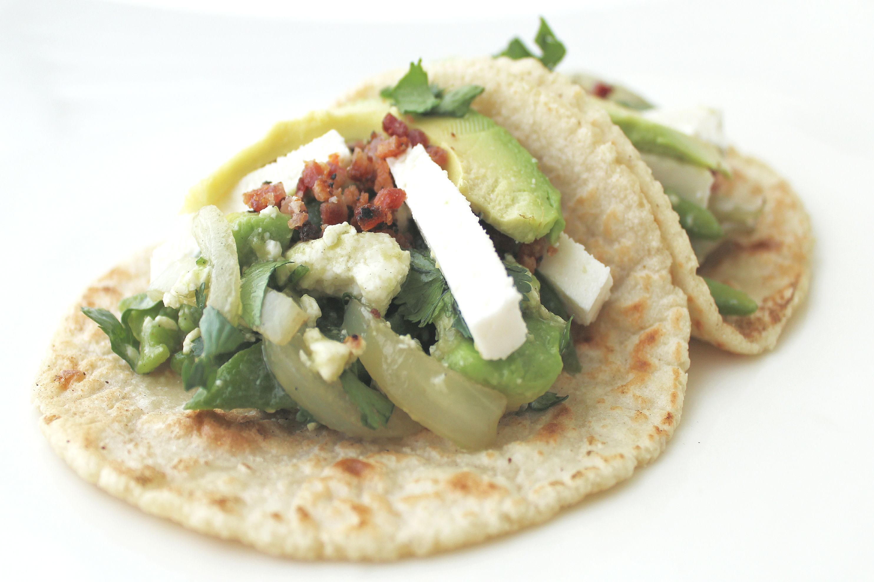 """Introducing our latest monthly special """"Taco El Desperado"""". Grilled rajas de jalapeño, queso panela, caramelized onions and ripe avocado topped with pepper encrusted bacon bits. Enjoy spicy, smoky flavors of Old Mexico in each bite. Available starting at our next food truck stop on Friday.  More info: http://www.sohotaco.com/2015/04/01/introducing-taco-el-desperado-our-april-taco-of-the-month #tacocatering #ocfoodies"""