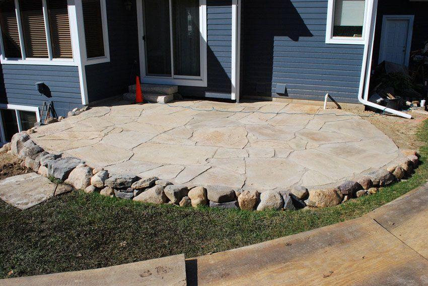 Backyard Stone Patio With Circular Design With Small Stone Edge