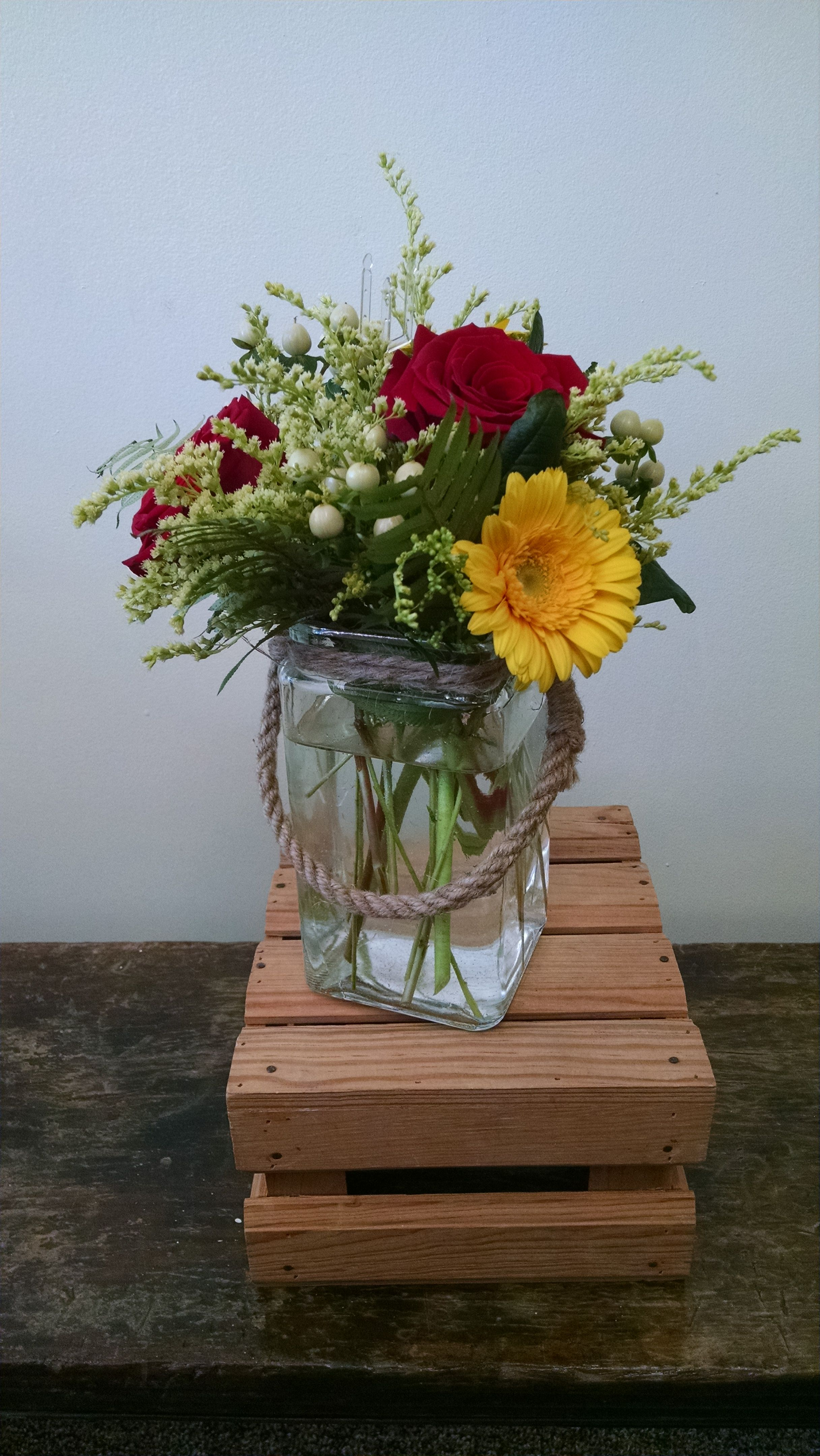 This arrangement features red roses, yellow Gerbera