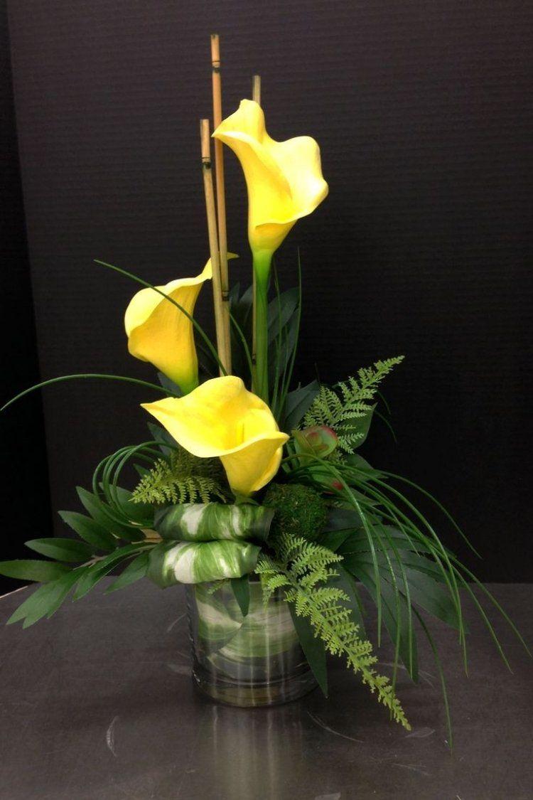 gelbe Calla mit grünem Farn in Glasvase arrangiert