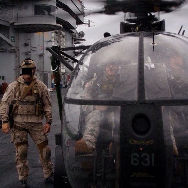 DEVGRU operator beside an MH-6 on the USS Nimitz