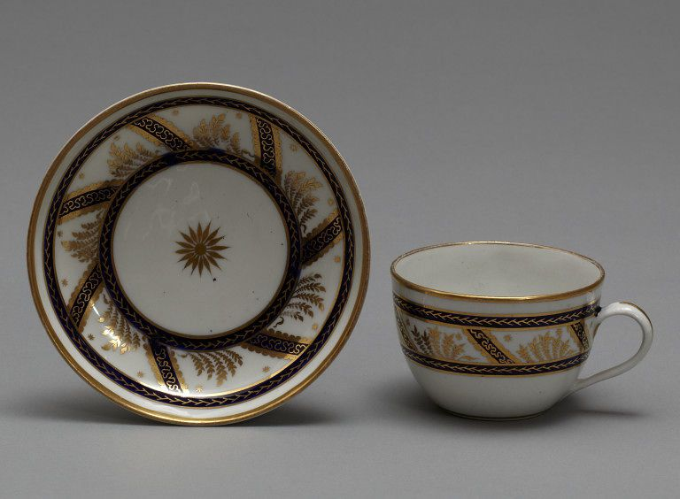 New Hall. Teacup and saucer; a coffee cup also in the set, see separate pin. Hard-paste porcelain painted in blue and gilded.  Decorated with diagonal bands between two concentric circles, in dark blue, over which is painted scrolls and foliations in gold. The interspaces are painted with leaves and stars in gold. In the collections of the V&A.