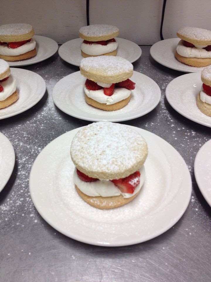 Strawberry shortcake willed with fresh sweetened cram and chopped strawberries, dusted with icing sugar