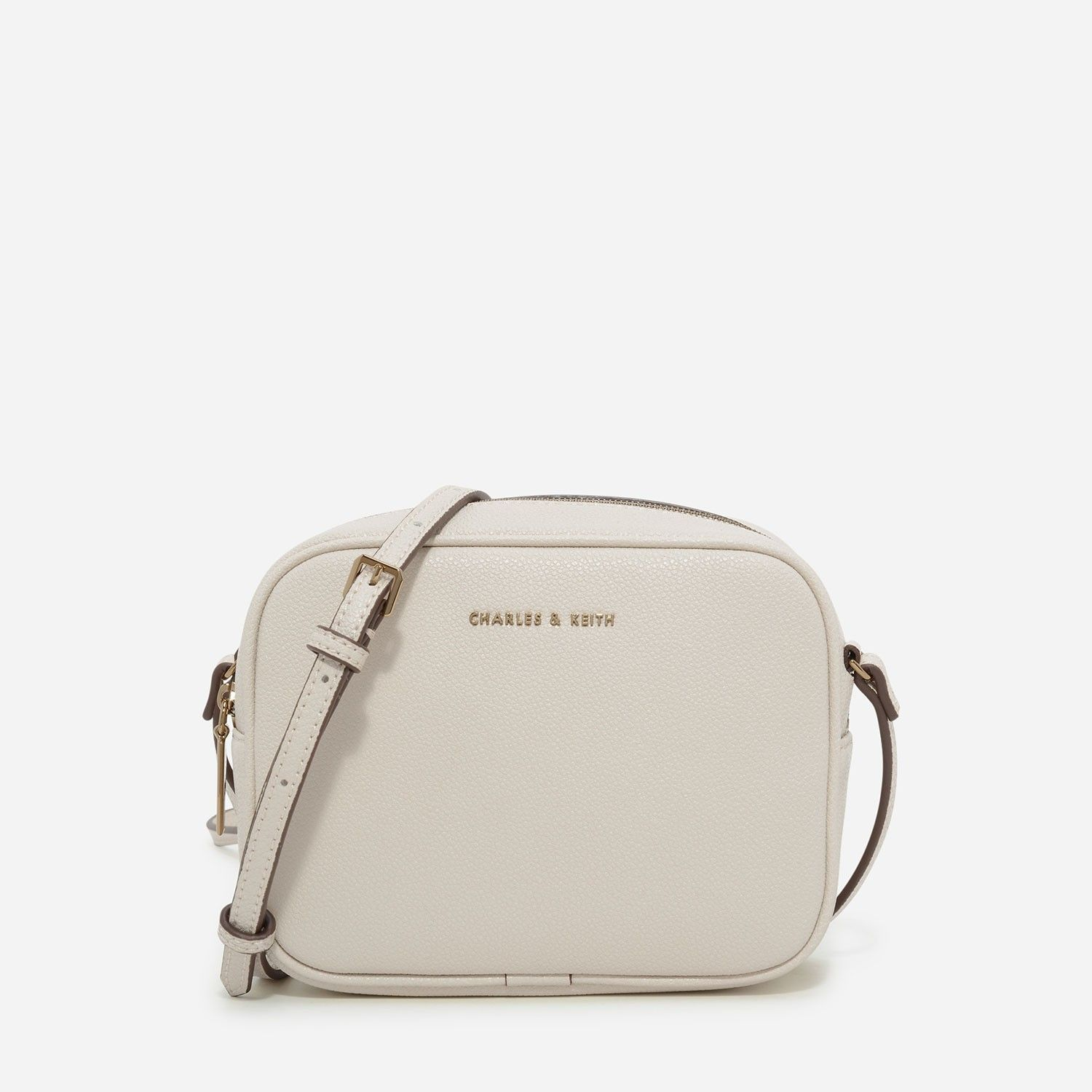 a324c3661201 CHARLES & KEITH - Bags. Ivory small-sized boxy textured sling bag featuring  curved edges. Fastens with a top zip closure.