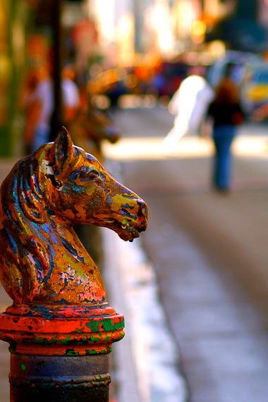 Years and years of colorful paint covering a horse hitch in the French Quarter, New Orleans.