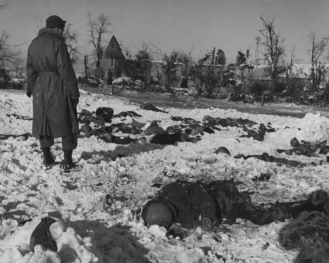 An American soldier looks numbly at bodies of American prisoners who were shot by Germans, near Malmedy, Belgium. December 17, 1944.