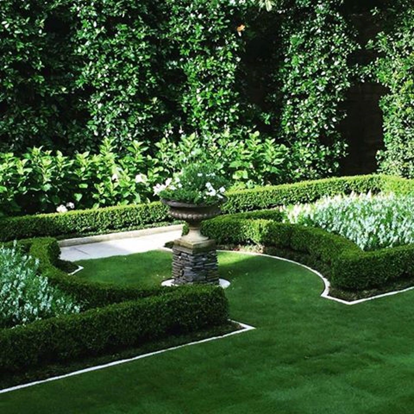 parterres enclose an oval of grass and an urn on a pedestal this