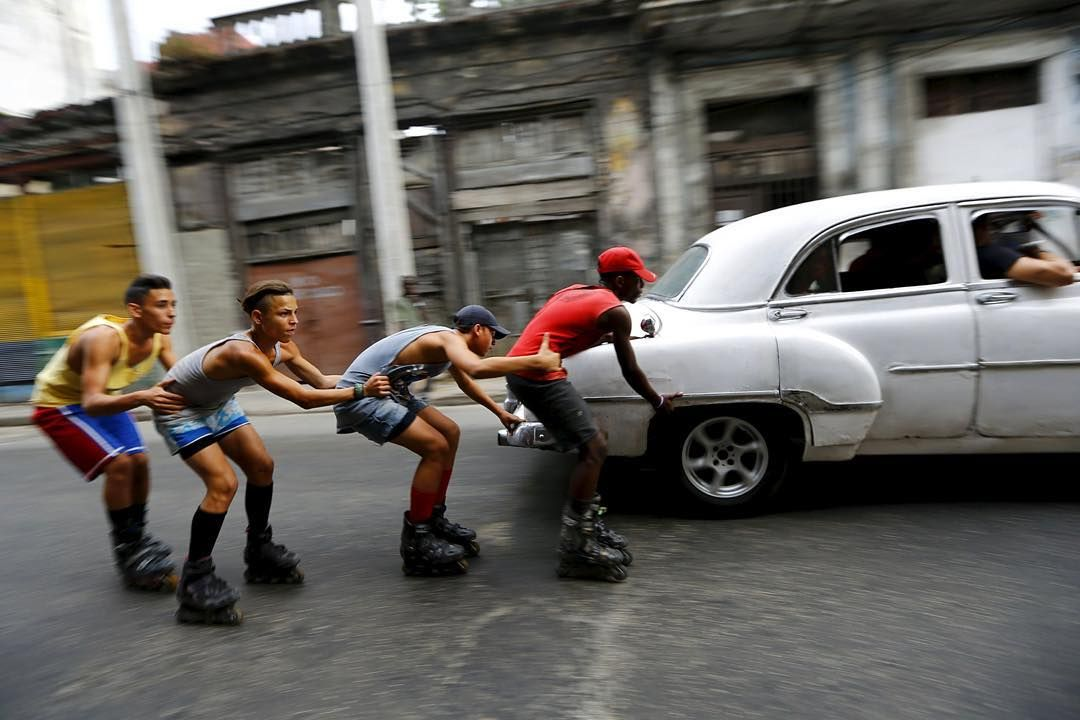 """21 MAR: Teenagers on roller skates hold on to each other as they are pulled by a vintage car to move along a street in Havana Cuba.  President Barack Obama is in Cuba for a historic three-day visit to the island and talks with its communist leader. He is the first sitting US president to visit since the 1959 revolution which heralded decades of hostility between the two countries. Speaking at the reopened US embassy in Havana he called the visit """"historic"""". Mr Obama will meet President Raul…"""