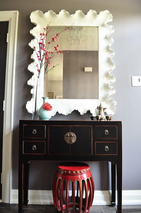 Detailed View Of The Foyer Shows A Red Drum Stool Tucked Under A
