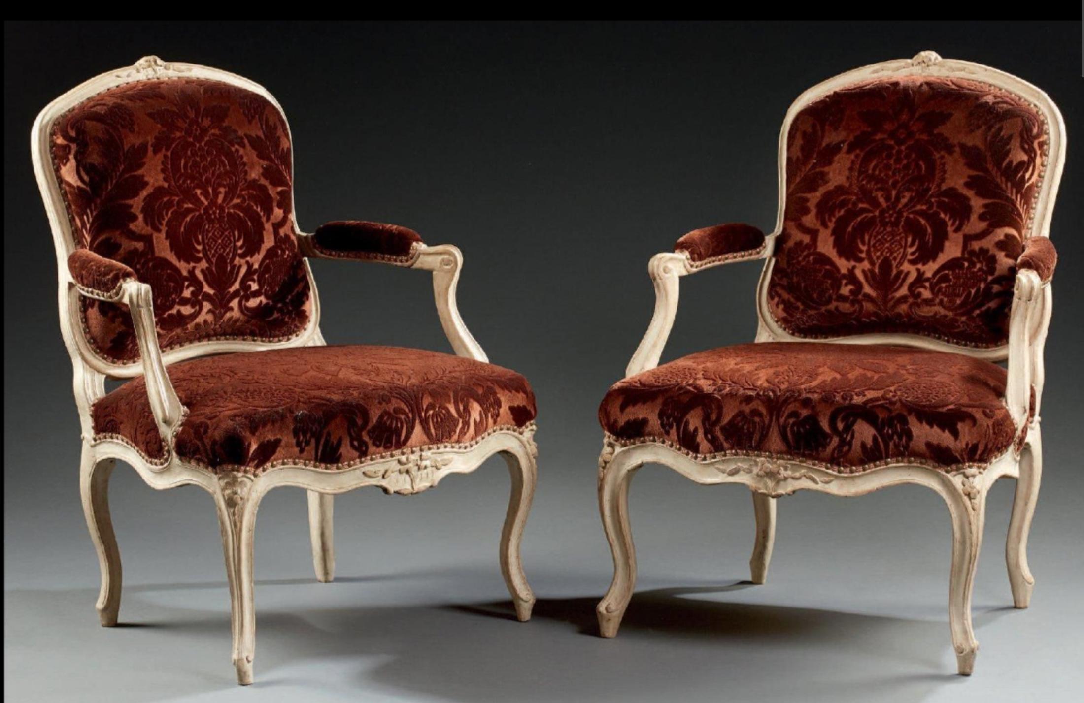 Paire de fauteuils à dossier plat en hêtre mouluré et relaqué crème agrémenté de fleurettes et feuillages stylisés; consoles d'accotoirs en coup de fouet; pieds cambrés. Estampille H. Amand et poinçon de jurande. Epoque Louis XV.