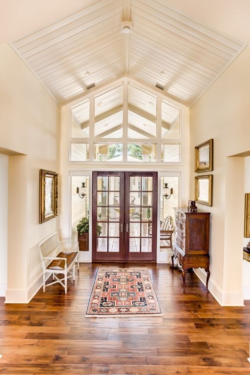 Traditional Entryway With Carpet Cathedral Ceiling Exposed Beam Hardwood Floors Staircase Design Foyer Ideas Entryway Foyer Design