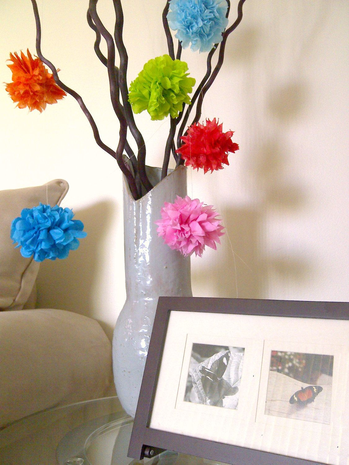 Tissue paper pom poms hanging from branches  Woodland party