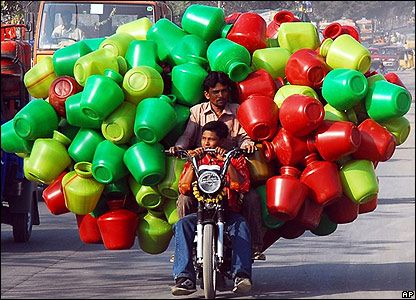 A motorcyclist laden with plastic pots in India