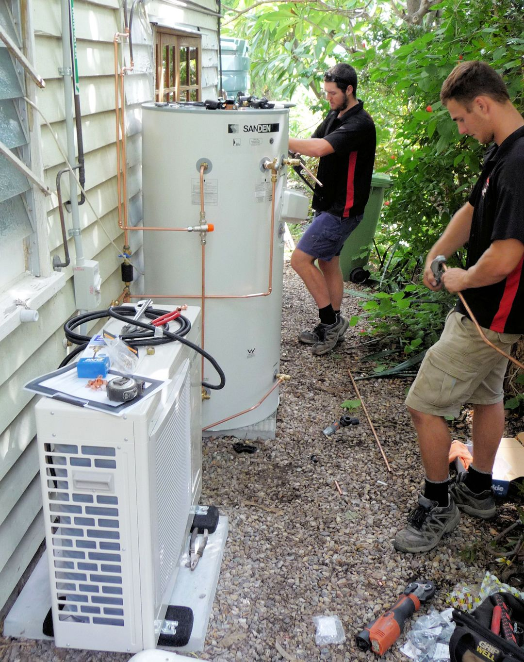 Photo Of Plumbers Installing A Sanden Heat Pump Water Heater Outside Compressor Heat Pump Water Hea Heat Pump Water Heater Water Heater Split System Heat Pump