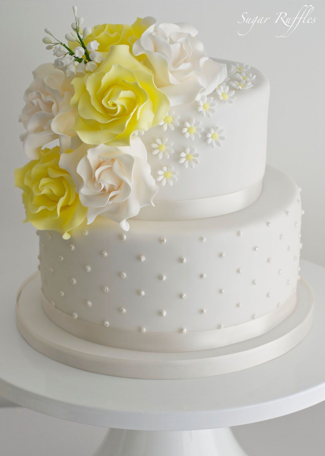 A 2-tier wedding cake with swiss dots, topped with a cascade of ...