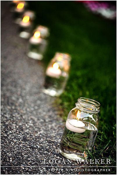 Photo of Mason jars with floating candles line the way to the reception in the back yard