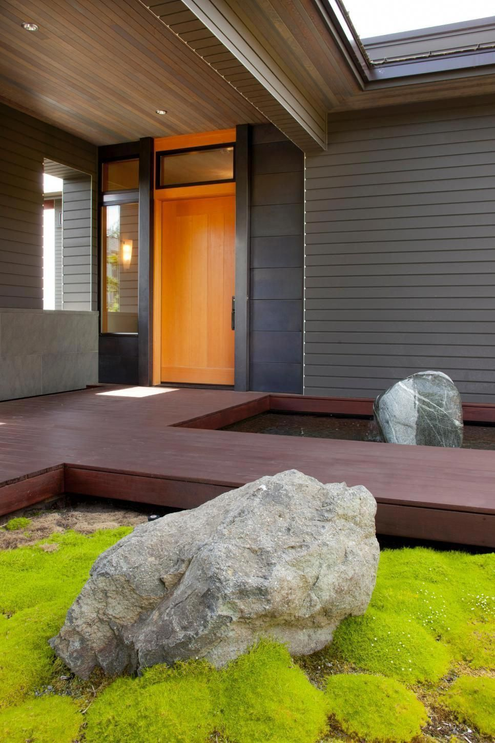 Large Boulders Flank The Dark Wood Walkway To This Contemporary Covered Porch A Sleek Wood Front Door With An Orange Tint Pops Against The Home S Gray Exterior Wood Front Doors Wood