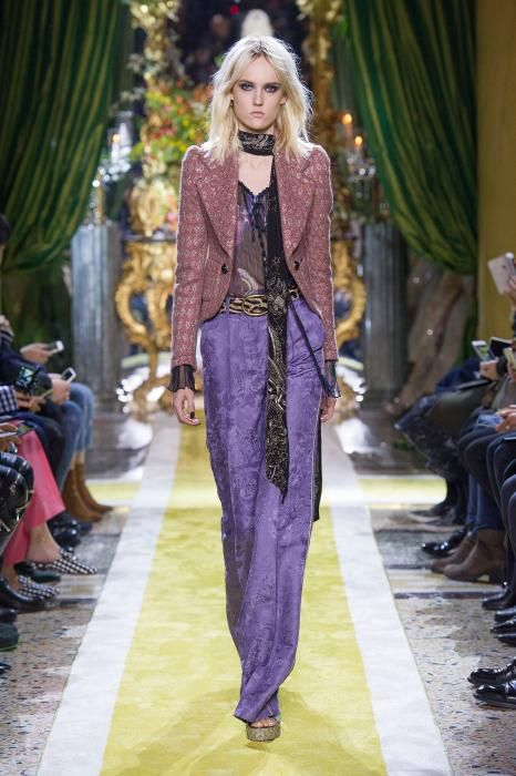 Roberto Cavalli, A/W 2016-2017. A female model wearing a long purple embroidered skirt, a light red, embroidered blazer, with a sheer black blouse, and thin black scarf with gold embroidery