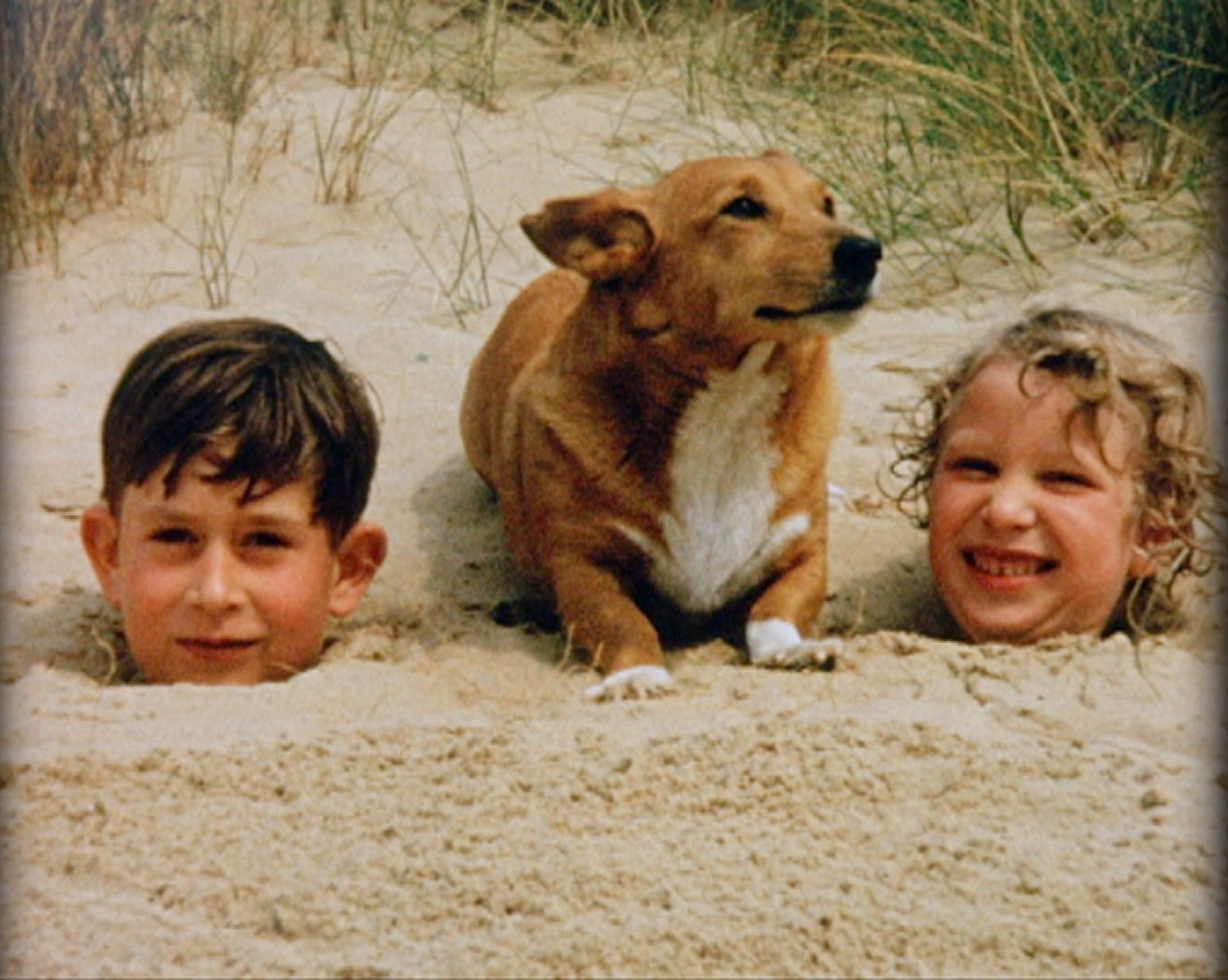 1957:  Prince Charles and Princess Anne buried in sand