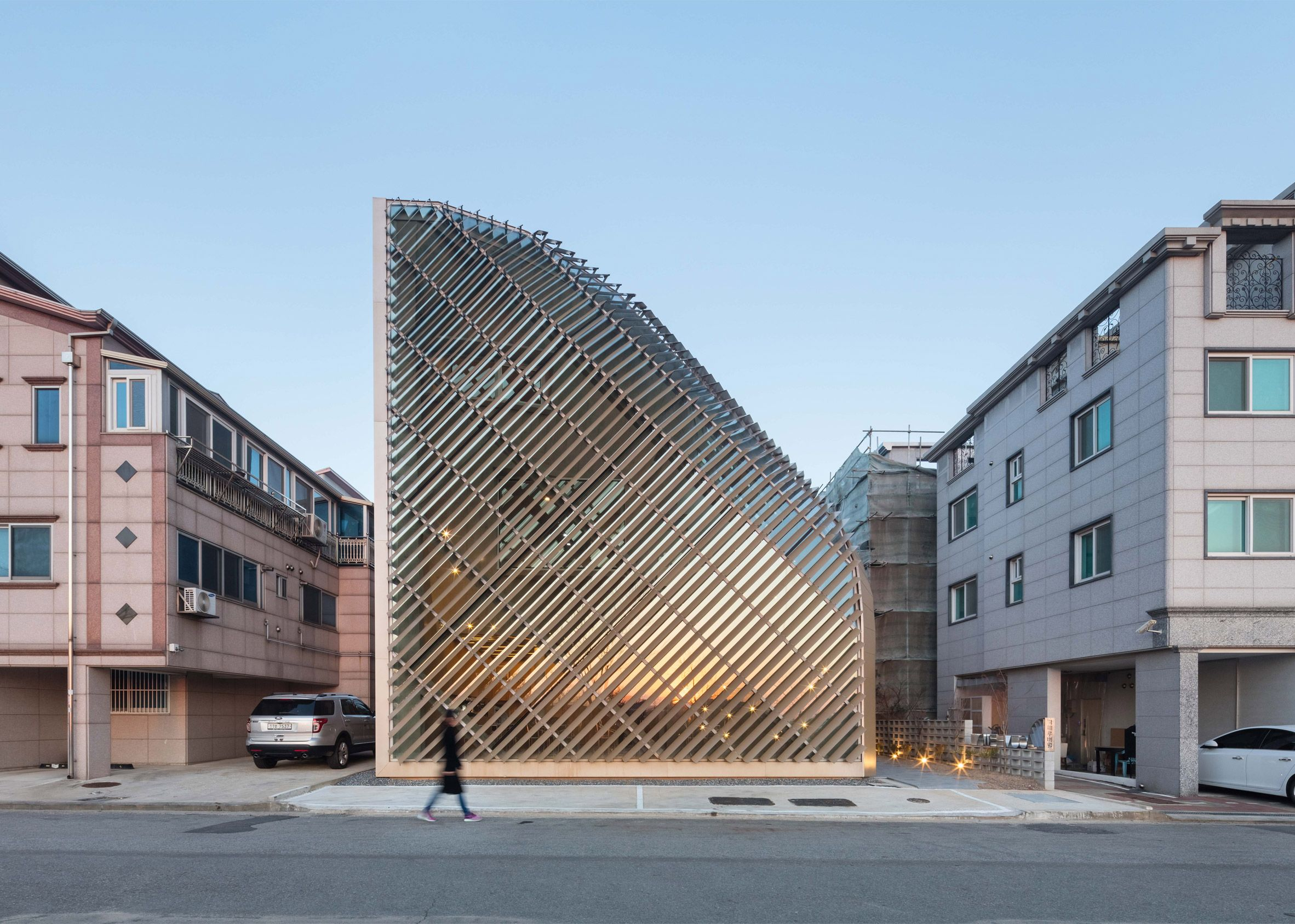 Slanted slats of aluminium cover the irregular, curving form of this house and cafe in Gyeonggi Province designed by South Korean architecture practice AND.