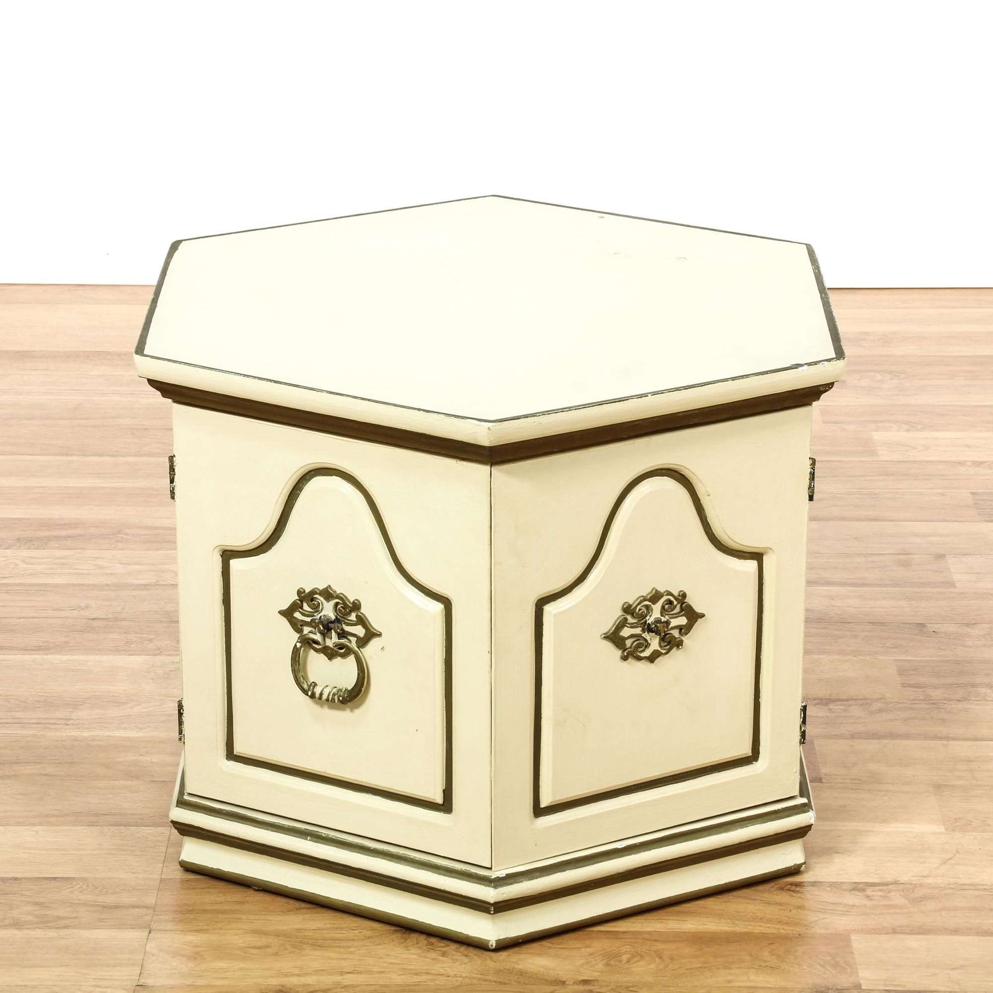 This hexagon end table is featured in a solid wood with a cream finish. This French Provincial side table has a cabinet w/ ample storage space, bronze accents, and steel handle pulls. Perfect for storing books! #european #tables #endtable #sandiegovintage #vintagefurniture