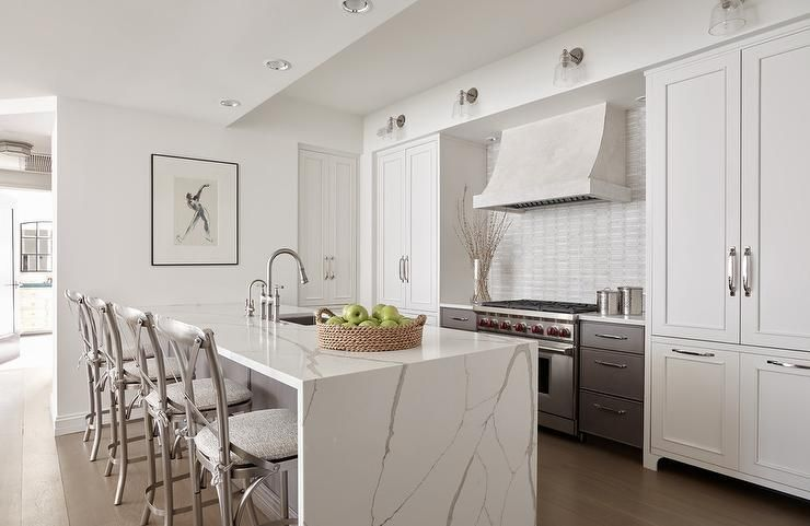 Calcutta Quartz Waterfall Countertop Island Along With Silver X Back Stools Incorporate Unrefined And Organic Materials Into A Contemporary Kitchen