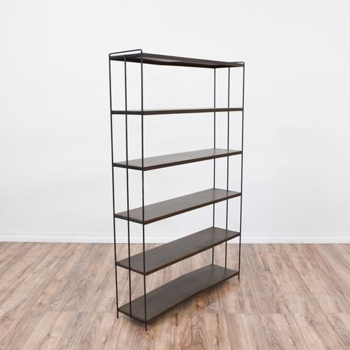 · This mid century modern bookcase is featured in a durable thin metal with a black finish. This tall bookshelf is in great condition with 6 dark wood shelves and a sleek modern design. Simple minimalist display shelf perfect for storing books and knick knacks!·Material: Metal, wood   ·Dimensions: 37x9.25x58   ·Condition: Very good   ·Number_of_pieces: 1   Available now on Loveseat.