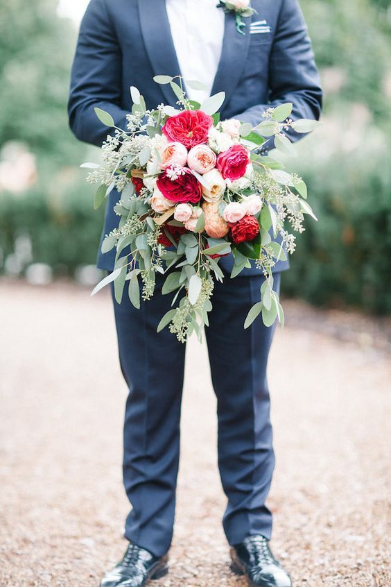 Love this picture of the groom holding his brides bouquet