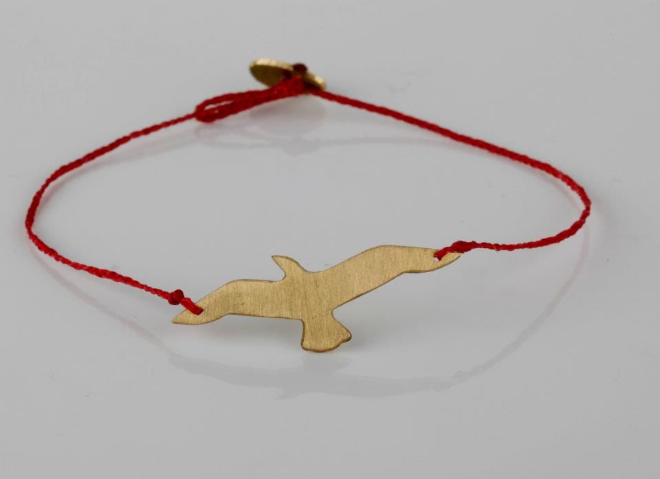 Brass hand cut 'bird in flight' charm on red silk with brass clasp.    R170