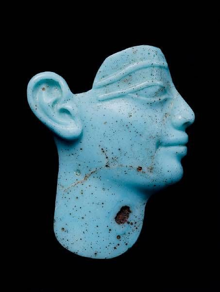 An Egyptian turquoise glass male head inlay. Probably Ptolemaic, circa 3rd-1st Centuries B.C.