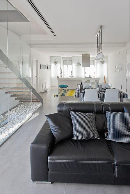 Chiralt Arquitectos I Salón-comedor con escalera de peldaño de madera flotante con zanca metálica y barandilla de cristal.