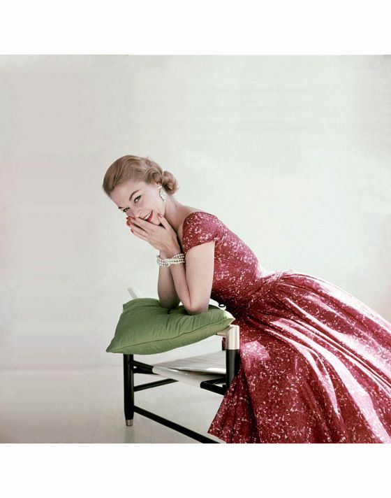 Jean Patchett in in red and pink floral print cotton chiffon dress with full skirt and small cap sleeves by Adele Simpson Vogue 1955