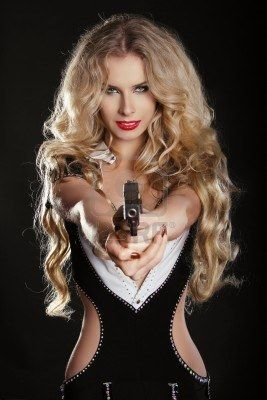 e5ae0fa494ee Sexy blond woman shooting gun isolated on black background Archivio  Fotografico