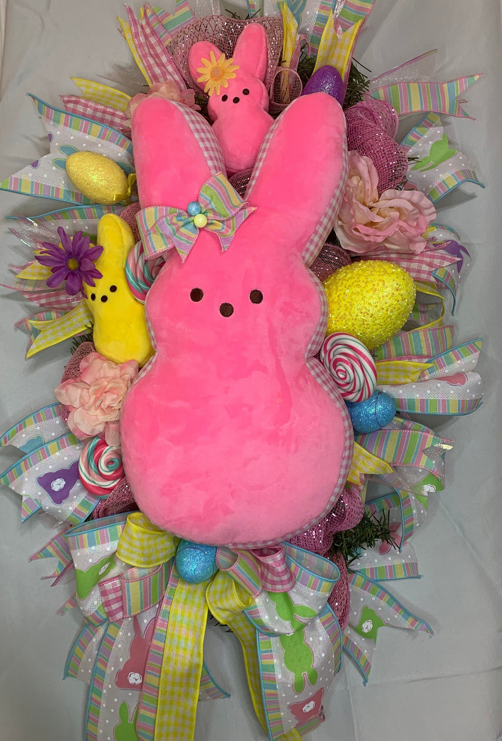 Easter Bunny Plush Peep Wreath, Easter Wreath, Easter Decor, Easter Swags, Door Decor - Easter swags, Easter wreaths, Easter bunny plush, Door decorations, Easter bunny, Bunny plush - Easter Bunny Plush Peep Wreath Wreath embellished with  colorful ribbon, 17  plush peep, and Flowers This beauty is perfect and will add to your Easter home decor  Sure to impress friends and family  All wreaths are handmade, and very detailed   Only quality products used to ensure your money worth Ready to ship Very carefully package, so it arrives just as you see it in the pictures  Wreath is shipped in a large corrugated box that is secure to protected and minimize damage that may occur while in transit I do recommend hanging this Wreath in a protected area if hanging outdoors  You will be able to enjoy your wreath for years to come if properly cared for  Use a door hanger or ribbon to hang this beauty up  Thanks for shopping with Pamela Creations Favorite my shop to see all new listing in your Etsy feed Instagram pamelas creation89 Facebook Pamela's Creation
