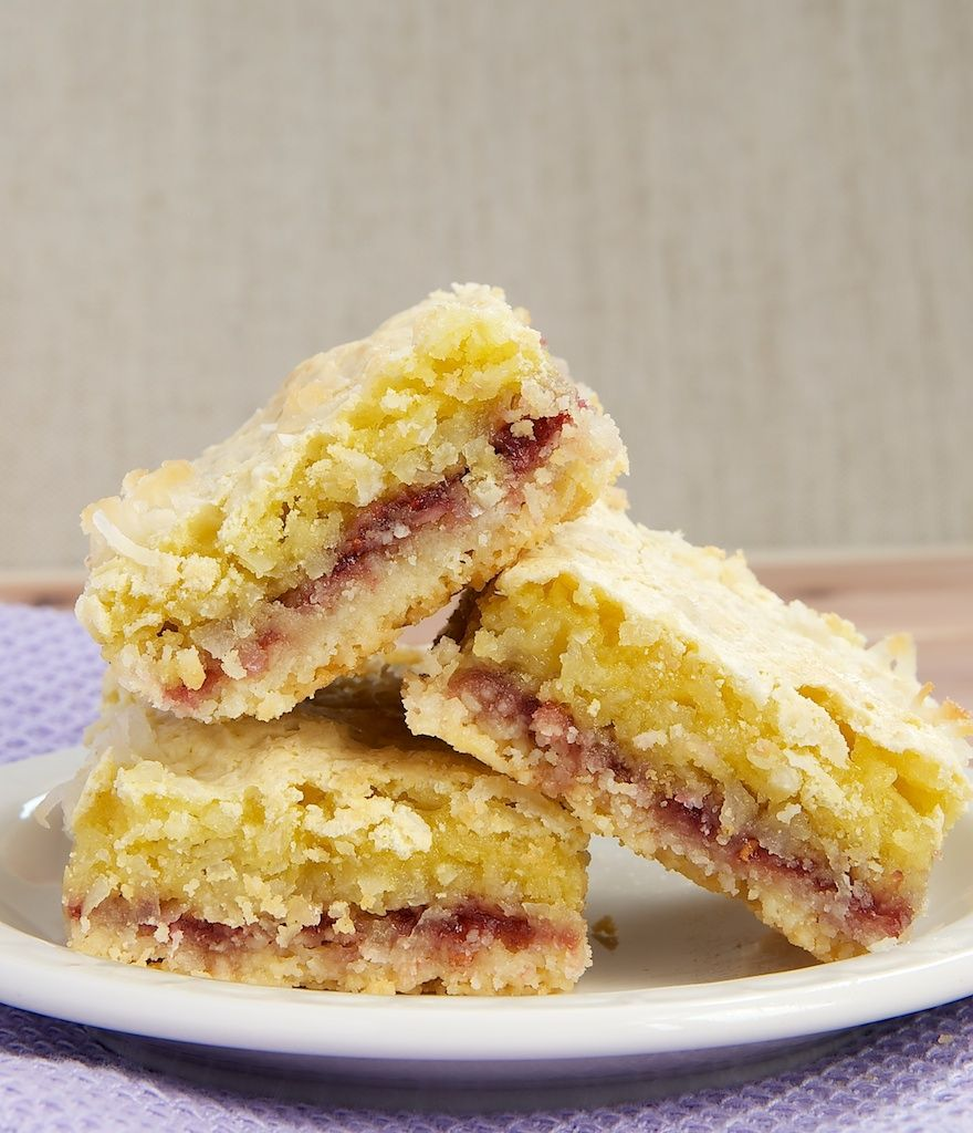 Coconut-Rasbperry Bars feature an almond shortbread crust, delicious raspberry preserves, and a chewy coconut topping.