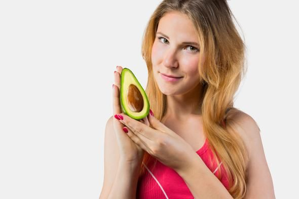 Young Woman Holding an Avocado